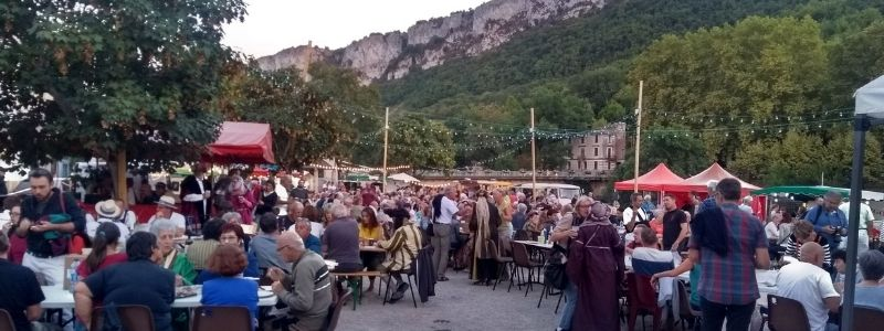 A picture of the marche gourmand in St Antonin Noble Val. People are sitting around tables enjoying a communal evening meal.